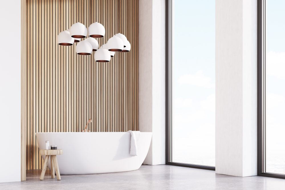 Corner of bathroom interior with a white tub, a chair with bodycare products and a lamp resembling grapes hanging above it. Light wood. 3d rendering.