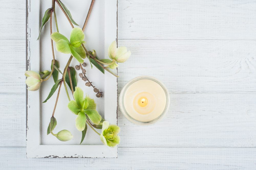 SPA composition with green flowers and lit candle on white wooden background. Top view